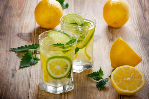 Lemon water with fresh lemons and green mint leaves.